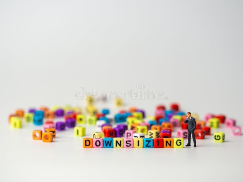 Miniaturzahl Geschäftsmann in der Stellungsrückseite der dunkelblauen Klage von buntem des Größenreduzierungsalphabetes und des d lizenzfreies stockfoto