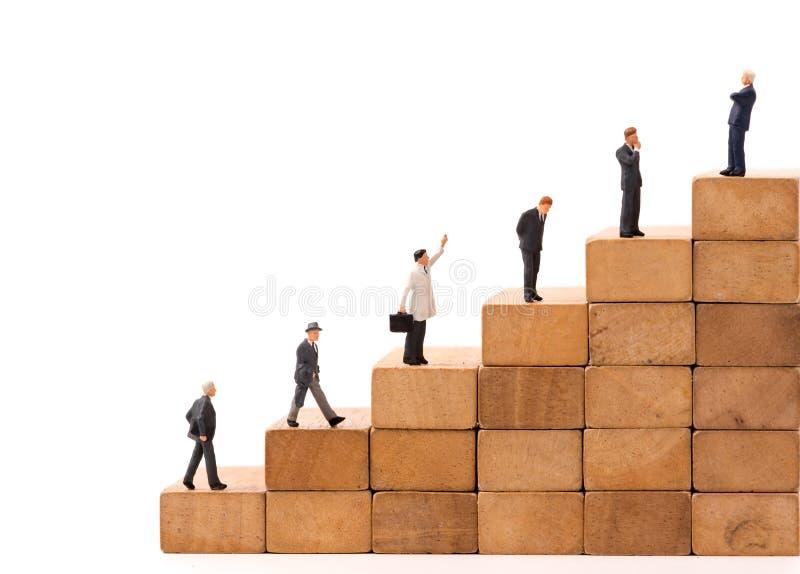 Miniaturzahl Leute Geschäftsmann, der auf hölzernem Block steht lizenzfreies stockfoto