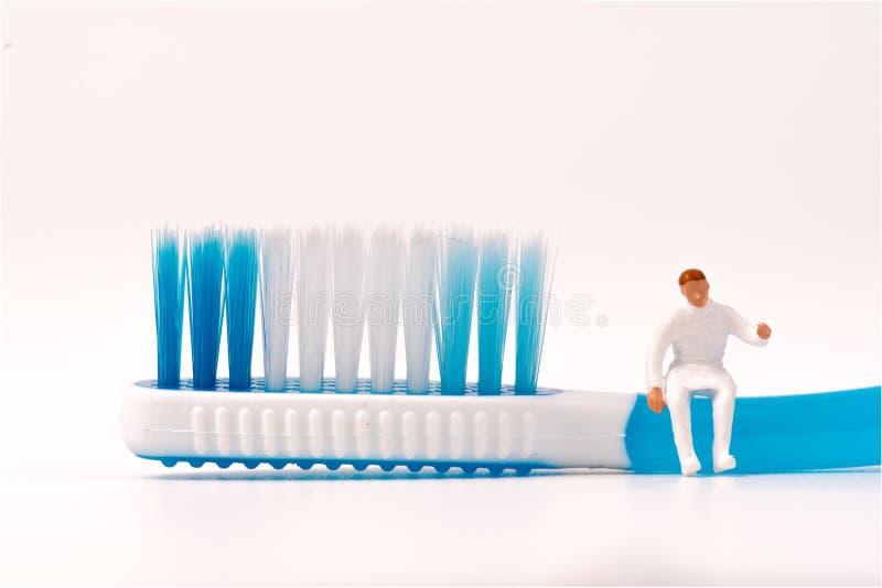 Miniaturzahl Leute mit zahnmedizinischem Werkzeug auf weißem Hintergrund lizenzfreie stockfotos