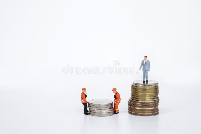 Miniatuur bedrijfsmens die zich op stapel van muntstuk en miniatuurarbeiders bewegend muntstuk bevinden stock foto's