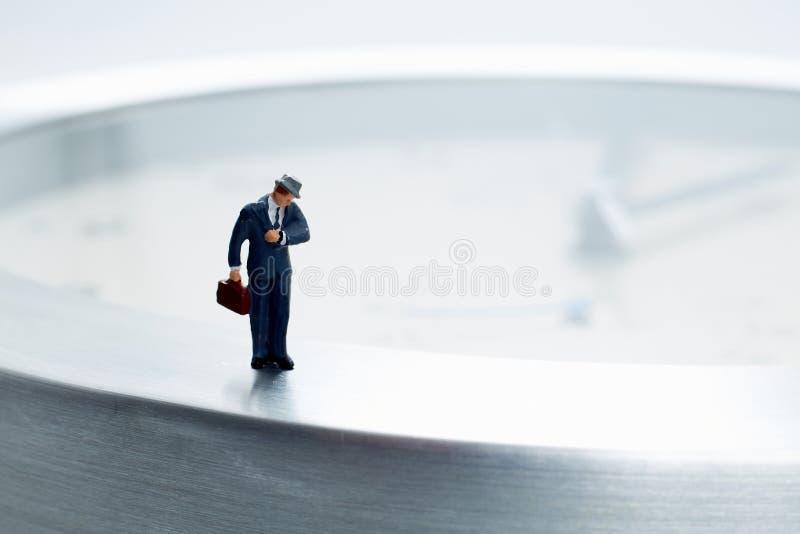 Miniatuur bedrijfsmens laat voor het werk royalty-vrije stock afbeeldingen