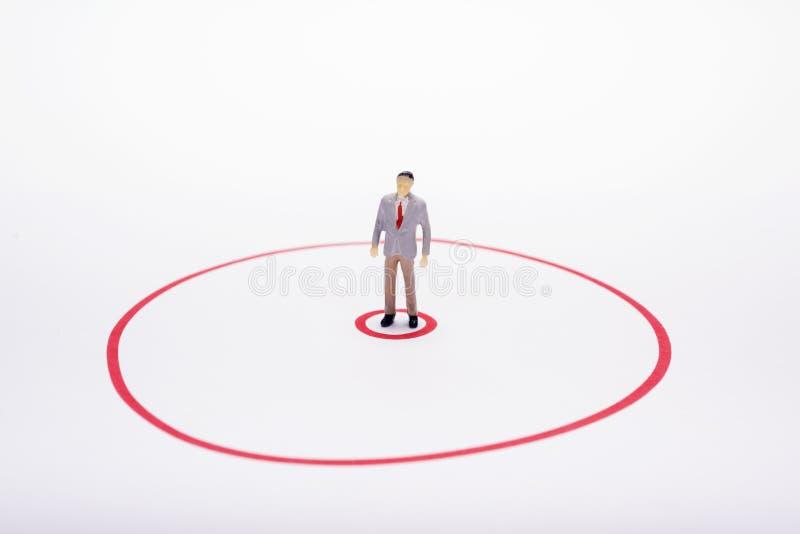 Miniatuur bedrijfsmens in rode cirkel over witte achtergrond of rug royalty-vrije stock fotografie