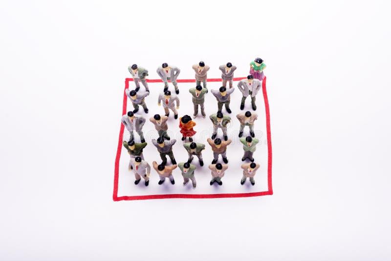 Miniatuur bedrijfsmensen in het vierkant van de conectionregeling over wit stock afbeeldingen
