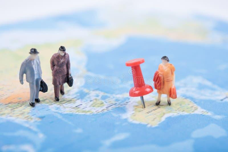 Miniatuur bedrijfsmensenreis op wereldkaart stock afbeeldingen