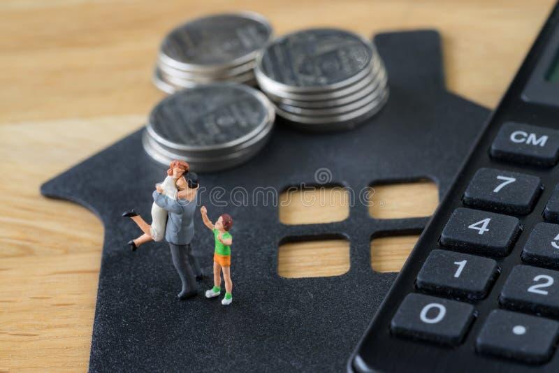 Miniatuur gelukkig familiecijfer die zich op document huis met calcu bevinden stock afbeeldingen