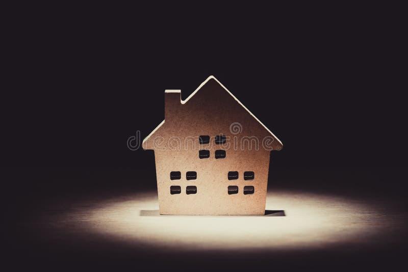 Miniatuur houten huismodel op houten achtergrond met verlichting effe stock fotografie