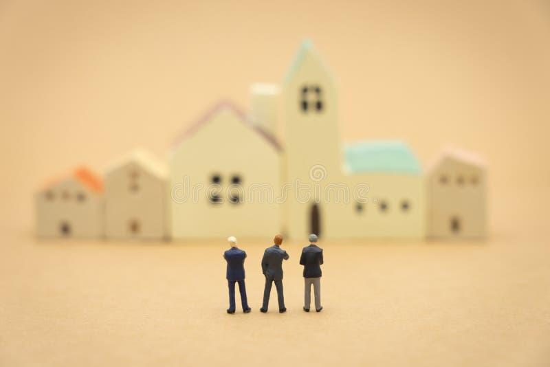 Miniatuur 3 mensenzakenlieden die zich met het achter Onderhandelen in zaken bevinden als achtergrond bedrijfsconcept en strategi stock afbeeldingen