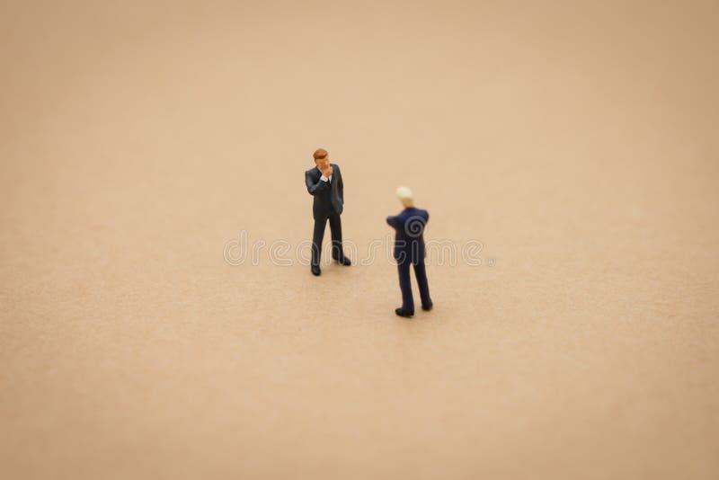 Miniatuur 2 mensenzakenlieden die zich met het achter Onderhandelen in zaken bevinden als achtergrond bedrijfsconcept en strategi stock afbeelding