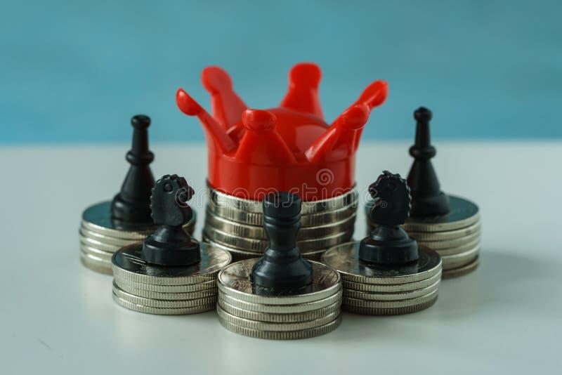 Miniatuur rode kroonkoning op stapel van muntstukken en schaaksymbool als F stock foto