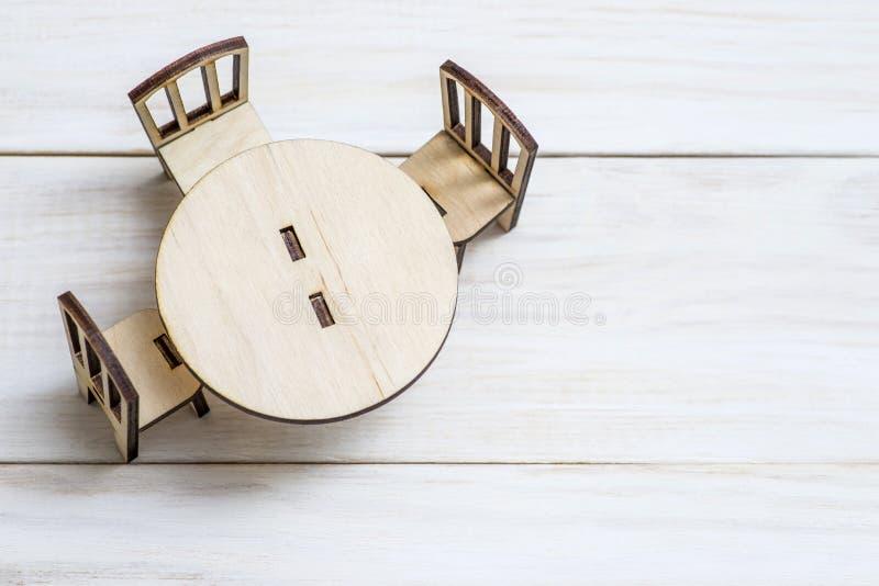 Miniatuur rustiek houten meubilair op houten achtergrond Uitstekende lijst en stoelen met exemplaarruimte stock afbeelding