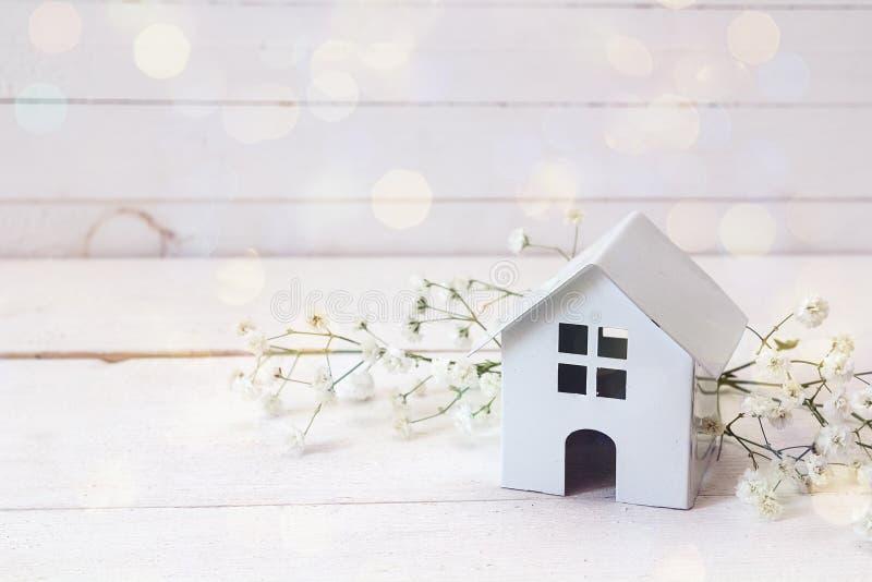 Miniatuur wit stuk speelgoed huis met bloemen op een witte houten backgro stock afbeelding