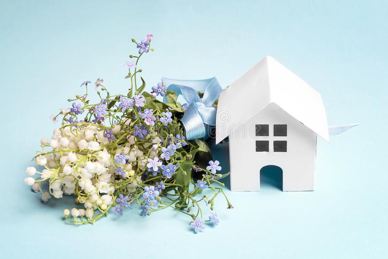 Miniatuur wit stuk speelgoed huis met boeket van lelietje-van-dalen en vergeet-mij-nietjes royalty-vrije stock afbeelding