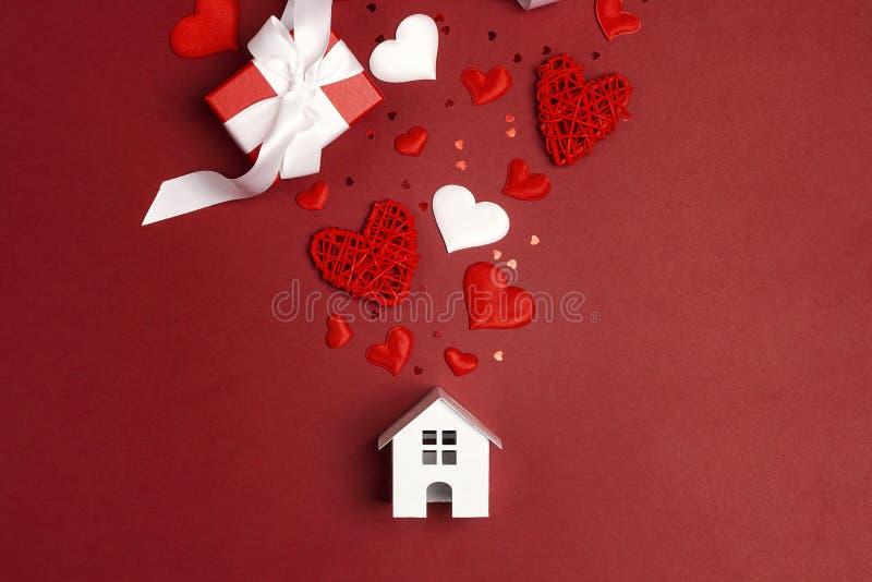 Miniatuur wit stuk speelgoed huis met harten en giften op rode achtergrond royalty-vrije stock foto