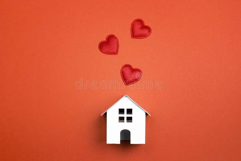 Miniatuur wit stuk speelgoed huis met harten op rode achtergrond stock afbeeldingen