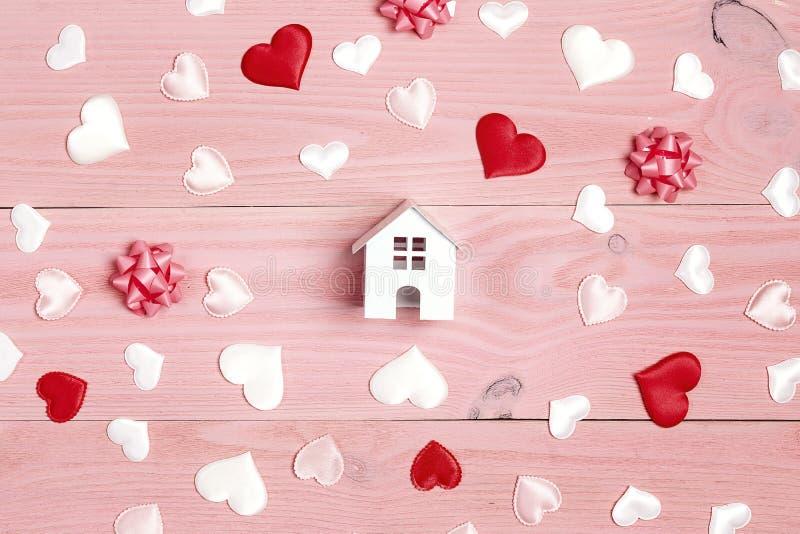 Miniatuur wit stuk speelgoed huis met harten op roze houten achtergrond stock foto's