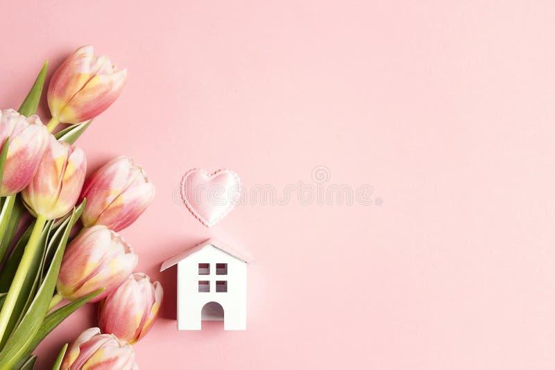 Miniatuur wit stuk speelgoed huis met tulpenbloemen op roze achtergrond stock foto