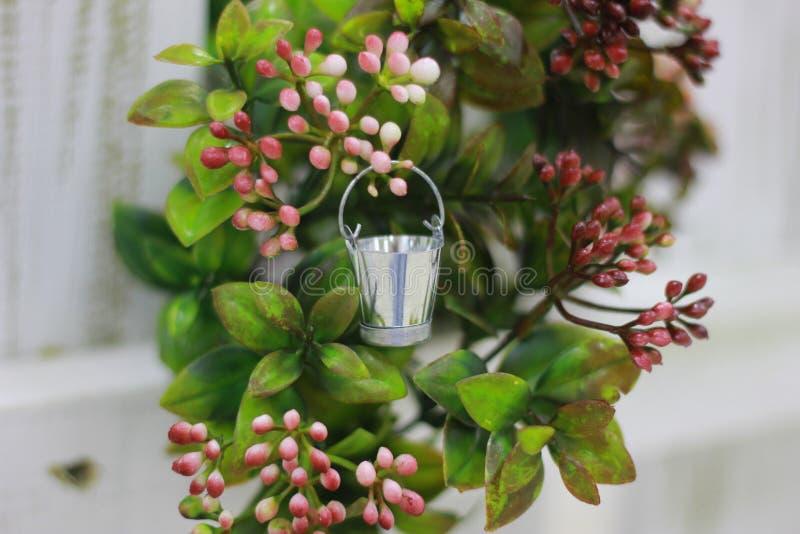 Miniatuuraluminiumemmer op groene achtergrond stock foto