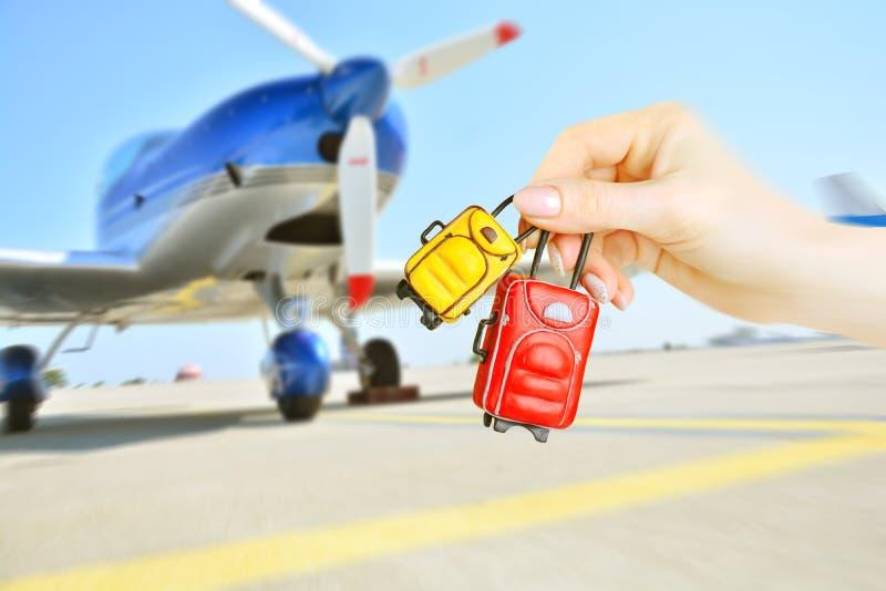 Miniatuurbagage in vrouwelijke handen op vage achtergrond met vliegtuigpropellor royalty-vrije stock foto