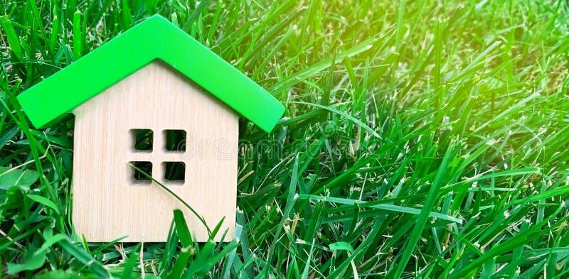 Miniatuurblokhuis op gras Concept 6 van onroerende goederen Milieuvriendelijk en energie efficiënt huis Het kopen van een huis bu royalty-vrije stock afbeelding