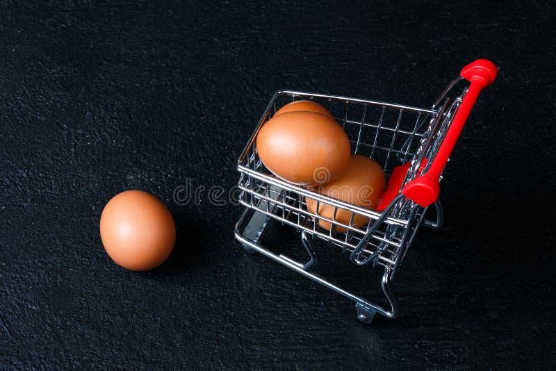 Miniatuurboodschappenwagentje met eieren stock afbeeldingen