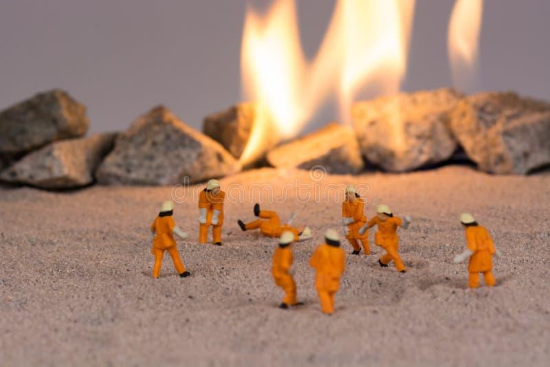 Miniatuurbrandweerlieden aan het werk dichtbij echte brand stock afbeeldingen