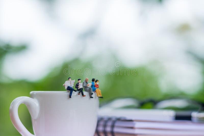 Miniatuurbusinessmans die boek op de kop van koffie readinging stock afbeelding