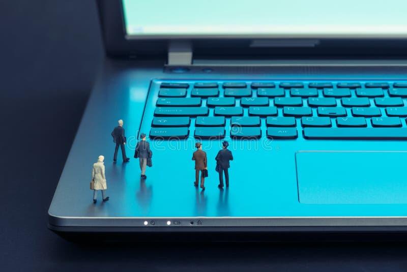 Miniatuurcijfers die op laptop lopen royalty-vrije stock afbeeldingen