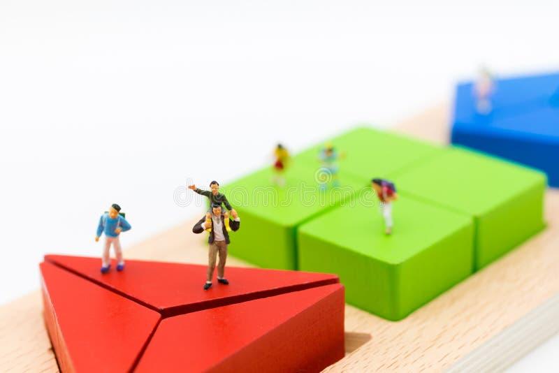Miniatuurfamilie: De vader gaf de zoon een rit op de hals en de kinderen bevinden zich rond stock foto