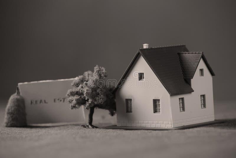 Miniatuurhuis met de nota van de onroerende goederenadvertentie royalty-vrije stock fotografie