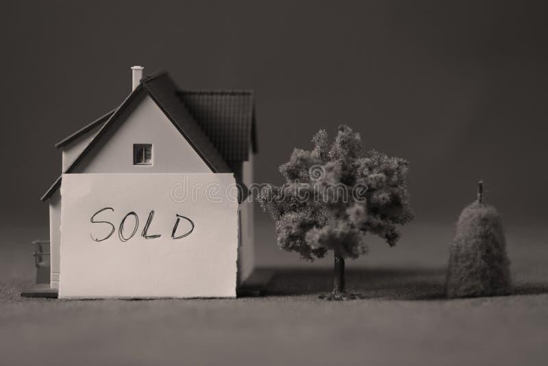 Miniatuurhuis met verkochte advertentienota stock afbeeldingen