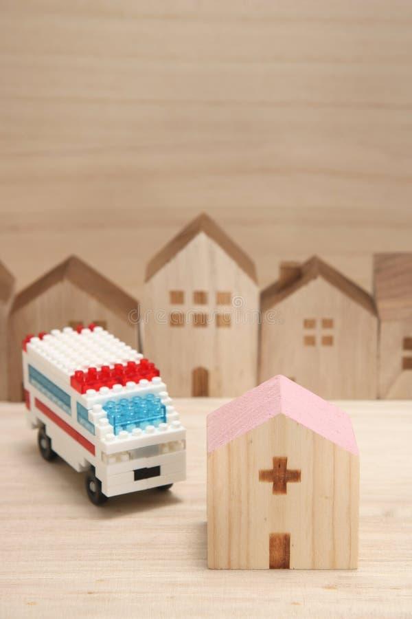 Miniatuurhuizen, het ziekenhuis en ziekenwagen op hout stock foto