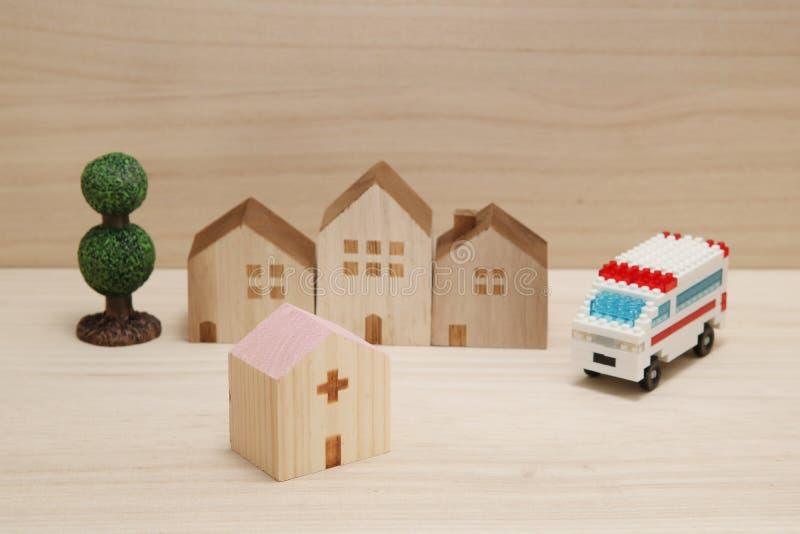Miniatuurhuizen, het ziekenhuis en ziekenwagen op hout stock afbeelding