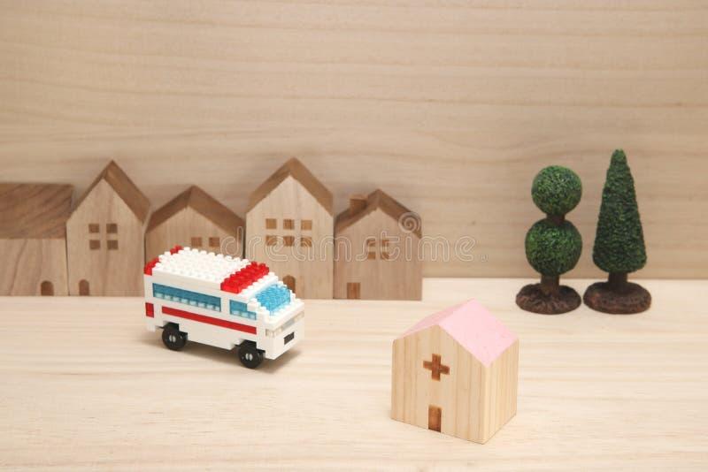 Miniatuurhuizen, het ziekenhuis en ziekenwagen op hout royalty-vrije stock foto