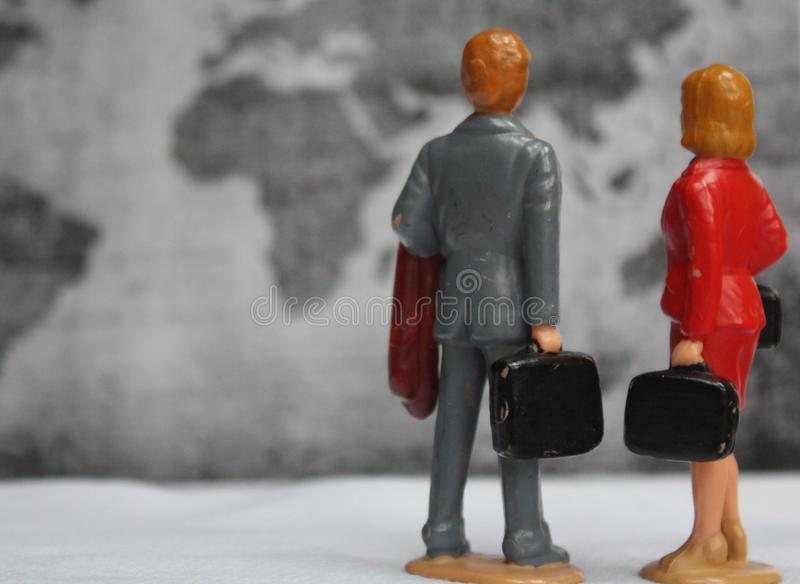 Miniatuurman en vrouw die met koffer op kaart van de wereld kijken, het concept van de reistoerist stock fotografie
