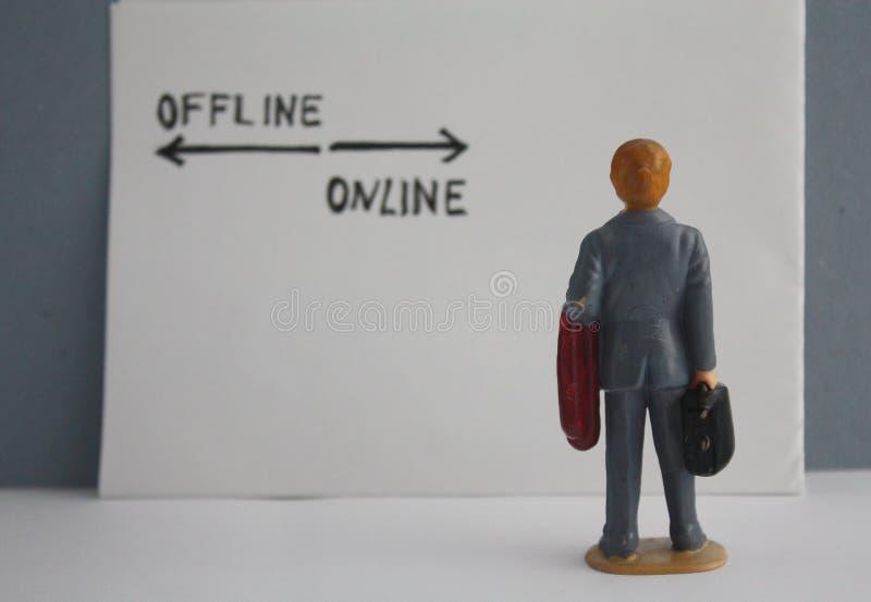 Miniatuurmens in grijze laag achtermening Het denken over online en off-line opties Bedrijfs marketing www concept royalty-vrije stock foto's
