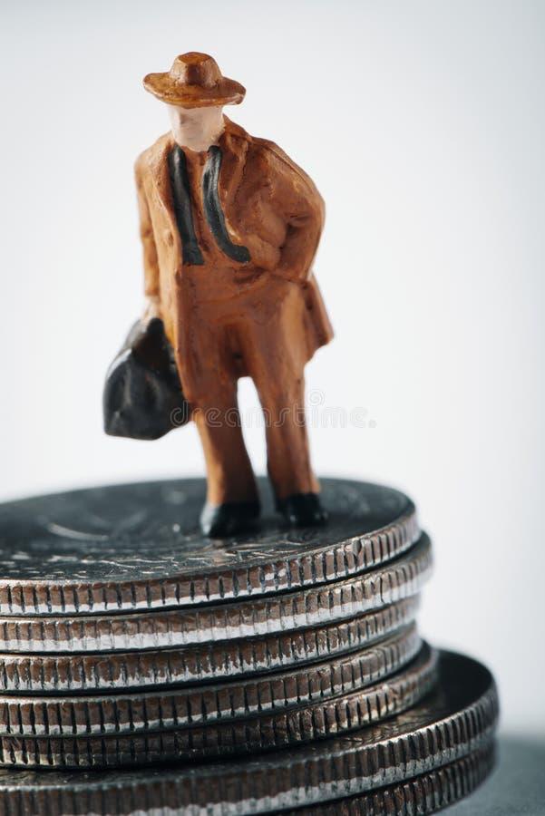 Miniatuurmens met een koffer op dollarmuntstukken royalty-vrije stock afbeeldingen