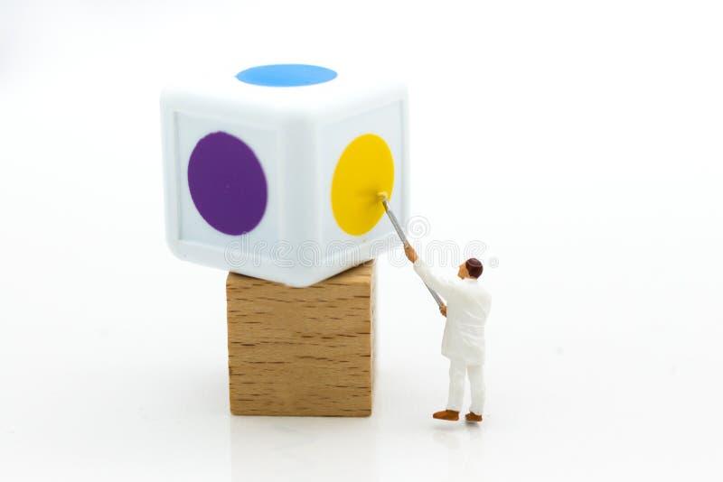 Miniatuurmensen: Arbeider het schilderen de kleur dobbelt  Beeldgebruik voor B royalty-vrije stock afbeeldingen