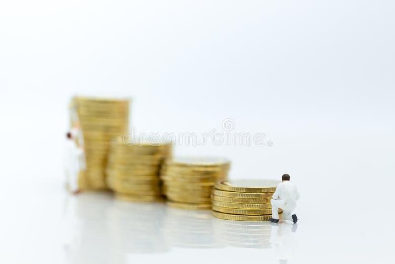 Miniatuurmensen: arbeider met stapel muntstukken Beeldgebruik voor investering, voordeel, bedrijfsconcept royalty-vrije stock foto's