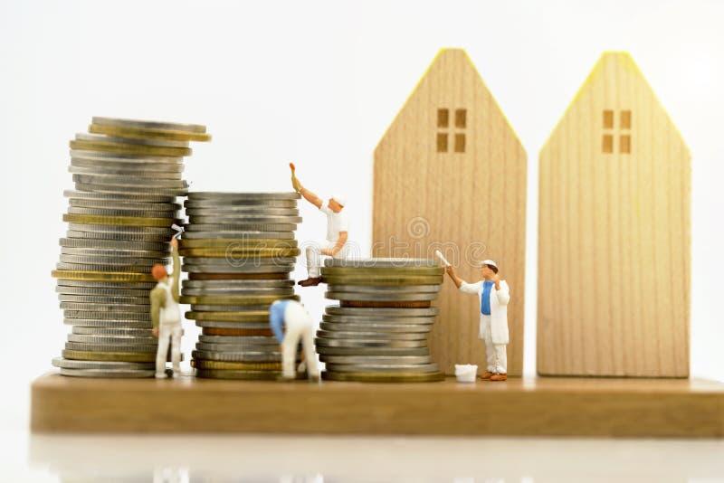 Miniatuurmensen: Arbeiders die kleur op muntstukkenstapel schilderen stock fotografie