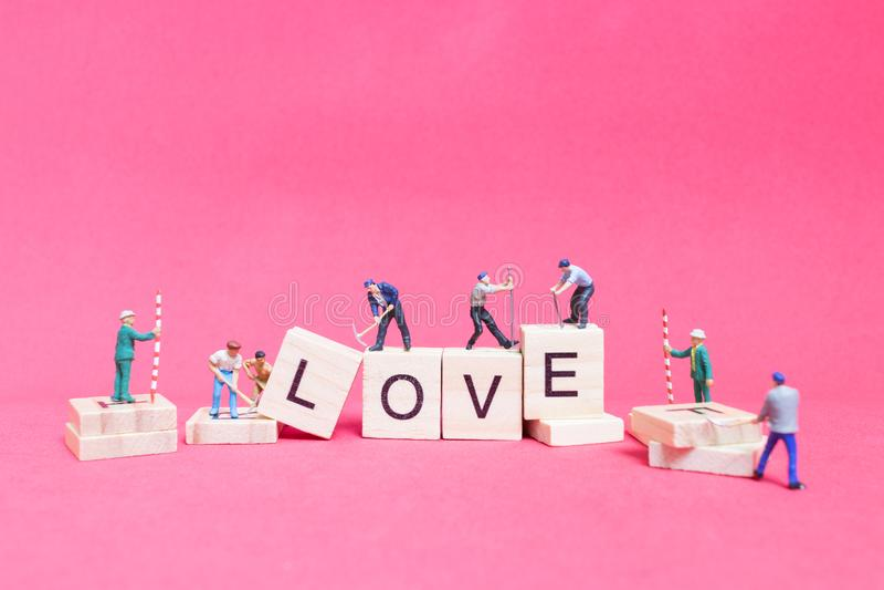 Miniatuurmensen: Arbeidersteam de Liefde ` van het de bouwwoord ` royalty-vrije stock afbeelding