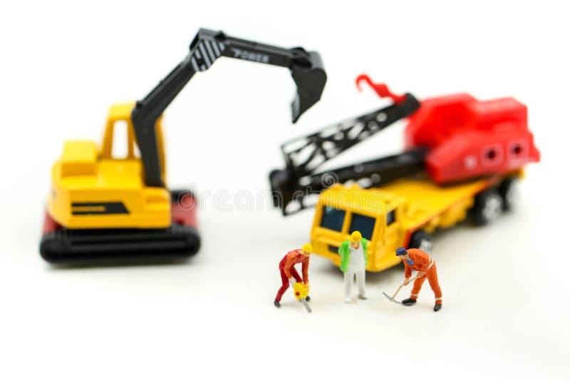 Miniatuurmensen: arbeidersteam voor de bouw van huis, Beeldgebruik voor stock afbeeldingen