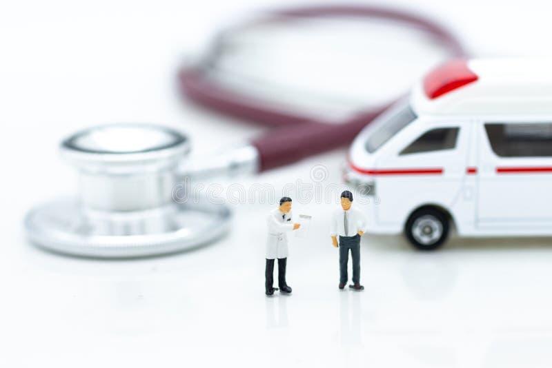 Miniatuurmensen, Arts met stethoscoop, ziekenwagen Beeldgebruik voor gezondheidsmedische behandeling van mensenconcept stock foto
