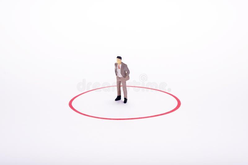 Miniatuurmensen, bedrijfsmens in rode cirkel over witte achtergrond stock fotografie