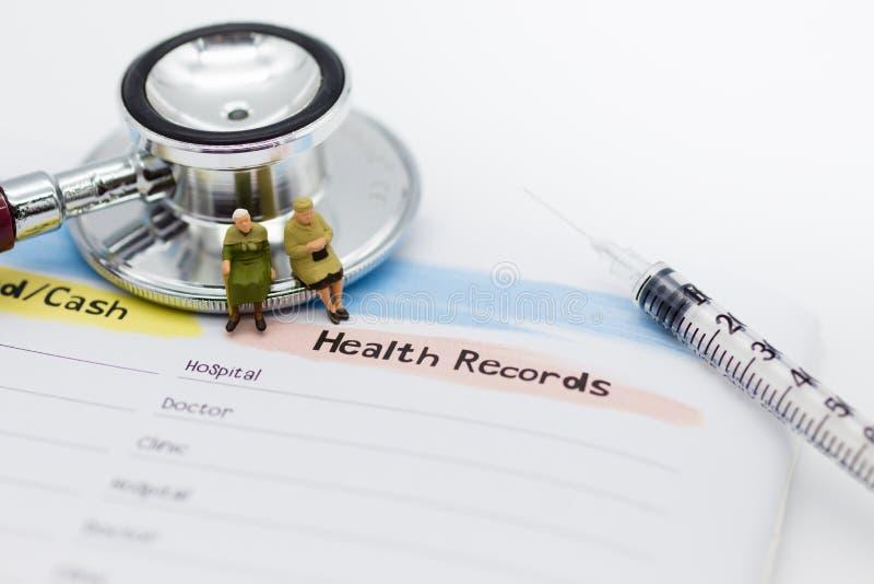 Miniatuurmensen: Bejaarden met jaarlijkse gezondheidscontrole Beeldgebruik voor gezond concept royalty-vrije stock afbeelding