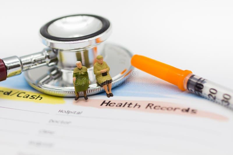 Miniatuurmensen: Bejaarden met jaarlijkse gezondheidscontrole Beeldgebruik voor gezond concept stock afbeelding