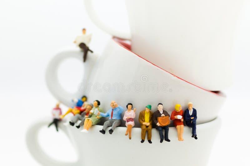 Miniatuurmensen: Commerciële teamzitting op kop van koffie en het hebben van een koffiepauze Beeldgebruik voor bedrijfsconcept stock afbeelding
