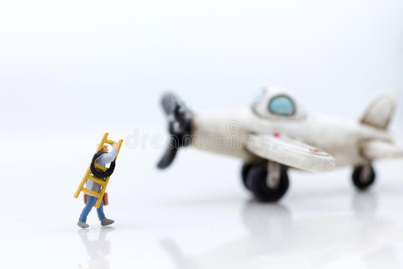 Miniatuurmensen: De arbeiders bereiden materiaal voor behoud van het vliegtuig voor Beeldgebruik voor behandeling, bedrijfsconcep stock foto