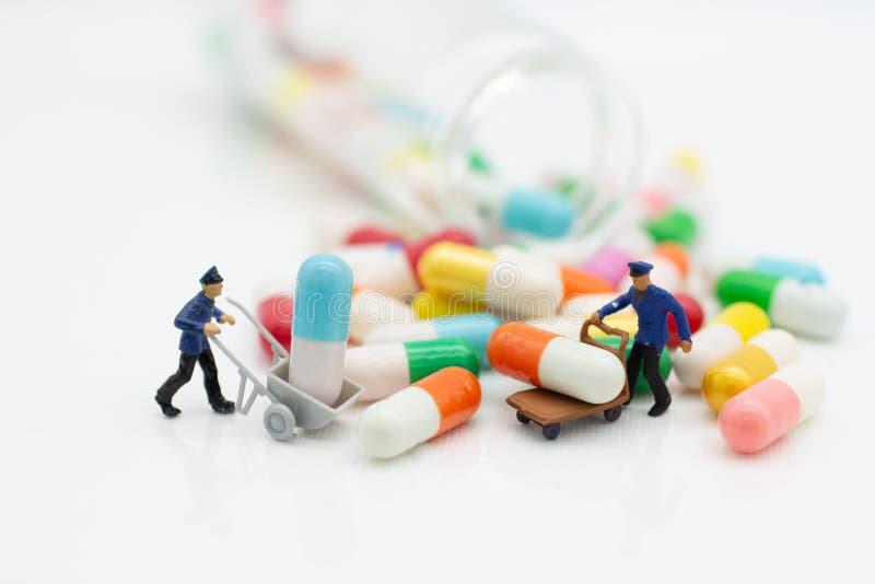 Miniatuurmensen: De arbeiders helpen aan het bewegen van drug Beeldgebruik voor gezondheidscontroleconcept stock foto