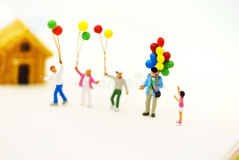Miniatuurmensen: de familie en de kinderen genieten van met kleurrijk ballons en huis royalty-vrije stock foto's