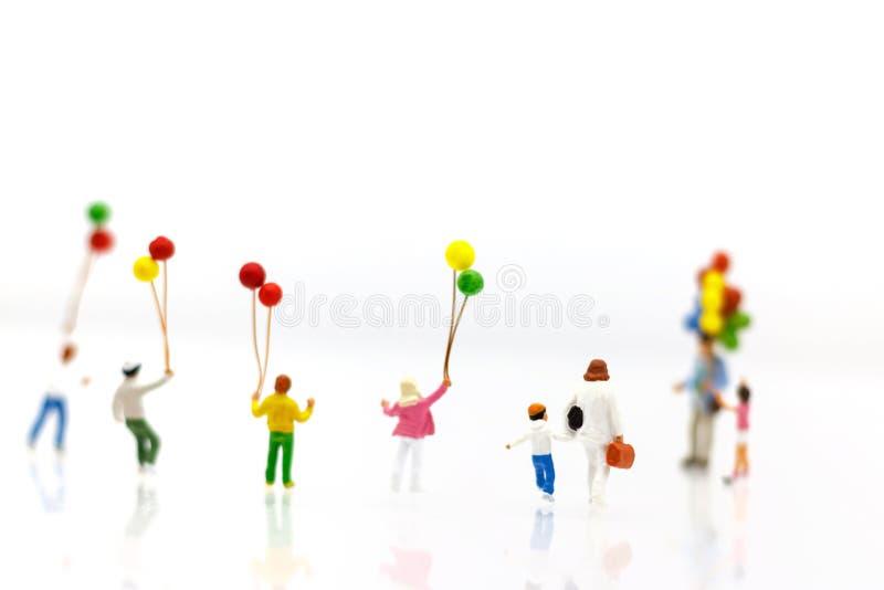 Miniatuurmensen: de familie en de kinderen genieten van met kleurrijke balloo stock afbeeldingen